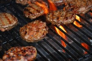 Hamburgers cooking on barbeque grill with flames